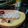 Hand pouring red wine into an ice cube tray